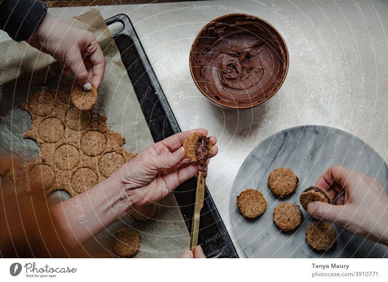 Familie macht vegane Sandwich-Kekse Selbstverpflegung Foodfotografie Vegane Ernährung Essen und Trinken Food-Styling Frau Backwaren Plätzchenteig Kekse backen