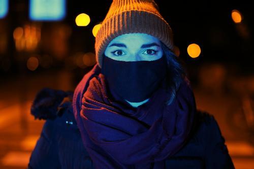 Junge Frau mit Maske und Mütze steht nachts mit blauem Licht angeleuchtet in orangem Laternenlicht in der Stadt Dschungel Jugendliche blaues Licht Straße