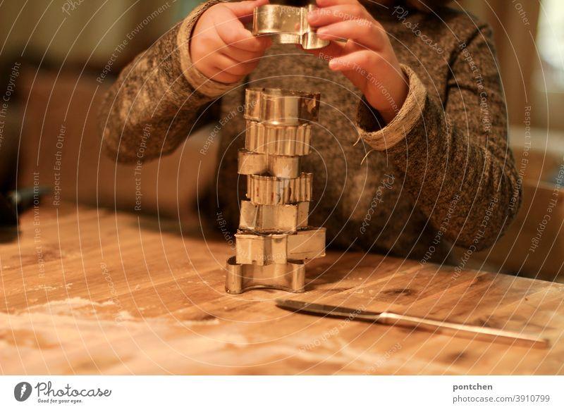 Ein Kind stapelt Plätzchenformen auf Mehl bestäubten Tisch.Vorweihnachtszeit, backen, Tradition ausstechen weihnachten hand tradition Weihnachten & Advent