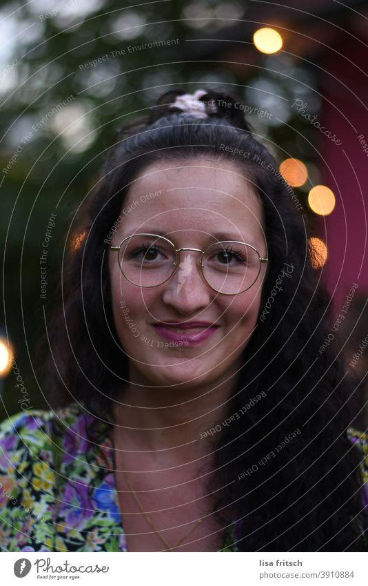 FRAU - SCHÖN - GRINSEN Frau 25-29 Jahre alt brünett Locken langhaarig Brille modern Lippenstift lichter tanz Erwachsene Außenaufnahme Farbfoto Abend