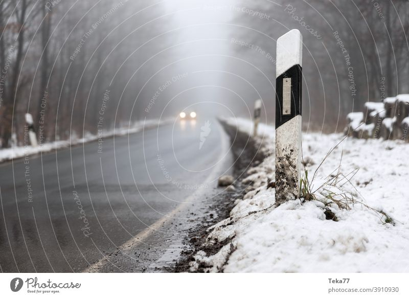 ein Auto, das auf einer nebligen Winterwaldstraße fährt Nebel Auto auf nebliger Straße Auto auf winterlicher Straße PKW Abend Fahrzeugbeleuchtung Auto in Gefahr