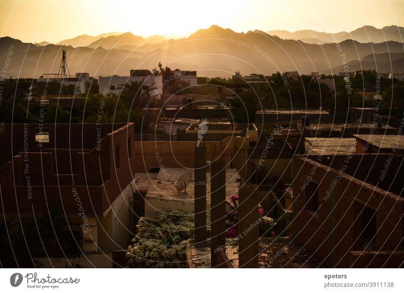 Blick über Dahab, Südsinai, Ägypten ins Landesinnere auf die Berge Süden Sinai Sinai-Halbinsel Nordafrika Sonnenuntergang unfertig Architektur Licht weich