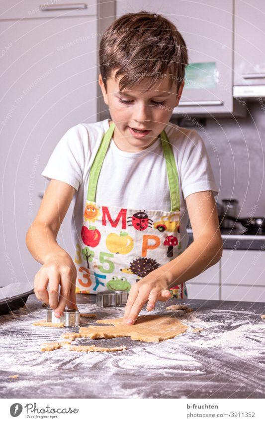 Kind beim Kekse ausstechen kind Küche Tisch Teig Mehl backen Plätzchenteig Weihnachten & Advent Ausstechform Plätzchen ausstechen Weihnachtsgebäck Backwaren