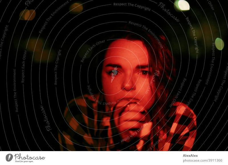 Junge Frau mit kariertem Hemd schaut nachts mit rotem Licht angeleuchtet in der dunklen Stadt in die Kamera Dschungel Jugendliche Straße Draussen Korkenzieher