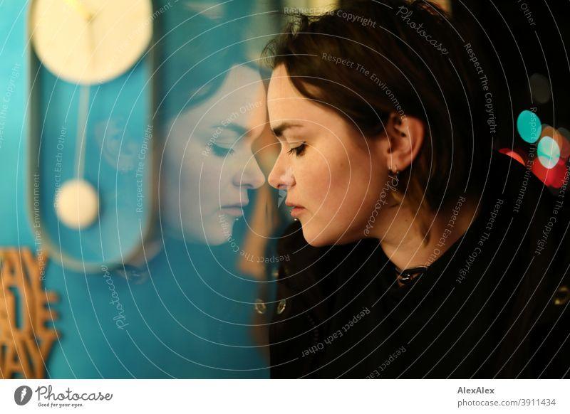 Junge Frau schaut nachts in ein Schaufenster und ihr Gesicht spiegelt sich darin Dschungel Jugendliche Straße Draussen Korkenzieher Stadt Stadtlandschaft dunkel