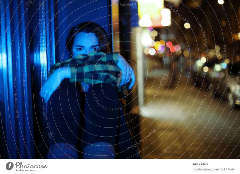Junge Frau sitzt nachts blau beleuchtet in einem Fenster auf einer bunt beleuchteten Strasse Dschungel Jugendliche blaues Licht Straße Karohemd kariert fenster