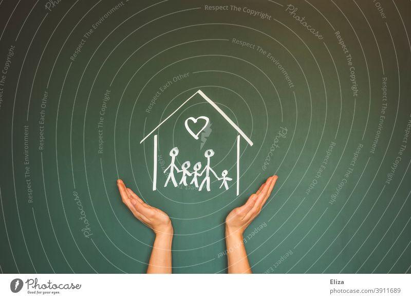 Konzept Familie zuhause. Eine Strichfiguren Familie in einem Haus mit Kreide auf eine Tafel gemalt zuhause bleiben Strichmännchen Eigenheim Kreidezeichnung