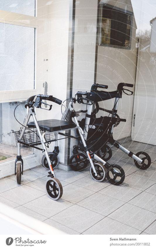Zwei Rollatoren stehen im Hausflur Gehhilfe Senior Mobilität alt Außenaufnahme Handicap Hilfsmittel Einsamkeit Farbfoto Tag Gesundheitswesen Alter festhalten