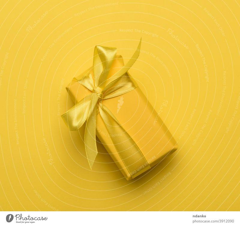 rechteckige Schachtel mit einem in gelbes Papier eingewickelten und mit einem gelben Seidenband gebundenen Geschenk festlich Kasten Gruß Feiertag sehr wenige