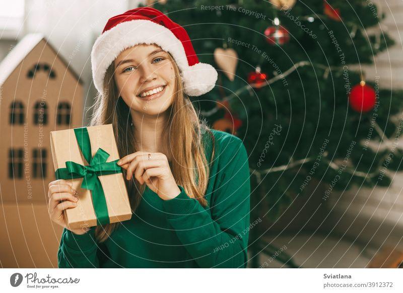 Ein hübsches kleines Mädchen schaut in die Kamera und lächelt. Sie hält ein Geschenk aus Kraftpapier, das mit einer grünen Schleife gebunden ist, in den Händen. Weihnachtsstimmung. Konzept für Neujahr Urlaub zu Hause.
