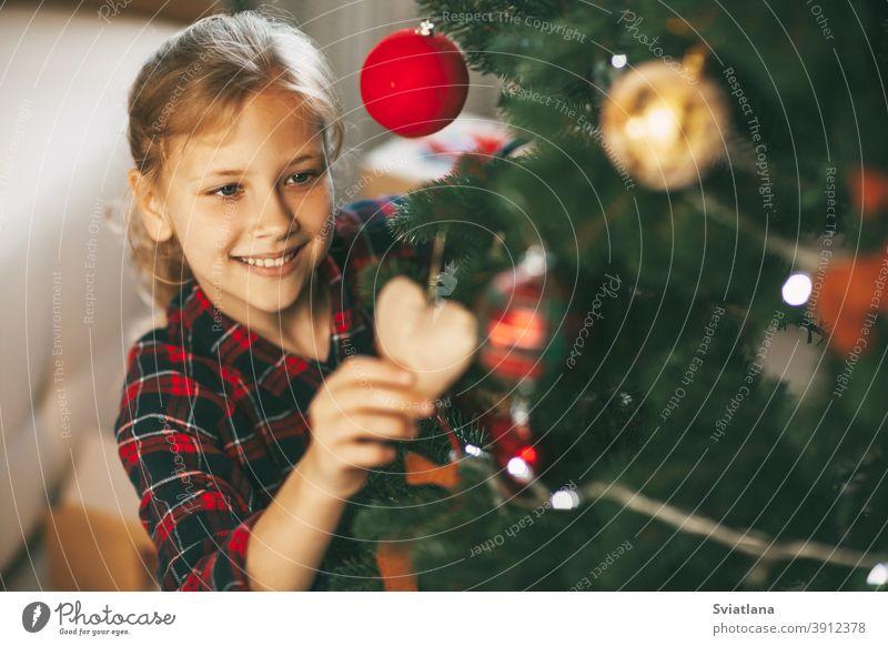 Glückliche kleine Blondine in Neujahrskleidung zu Hause, schmückt den Weihnachtsbaum und lächelt. Urlaub Konzept für Weihnachten und Neujahr zu Hause.