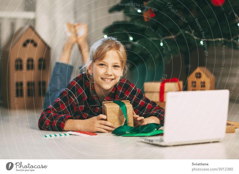 Ein glückliches kleines Mädchen öffnet ein Geschenk unter dem Weihnachtsbaum zu Hause und kommuniziert mit ihren Großeltern über einen Laptop per Videoverbindung. Feiertagskonzept für Weihnachten und Neujahr zu Hause.
