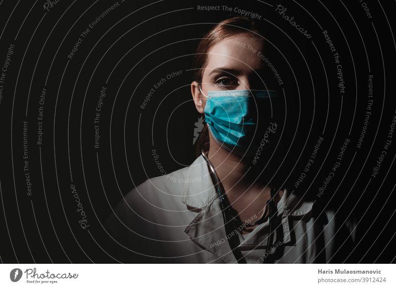 Ärztin mit Gesichtsmaske auf schwarzem Hintergrund Brasilien Korona-Epidemie Corona-Virus Coronavirus covid-19 covid-19-Test dunkel Arzt Ärzte Emotion Seuche