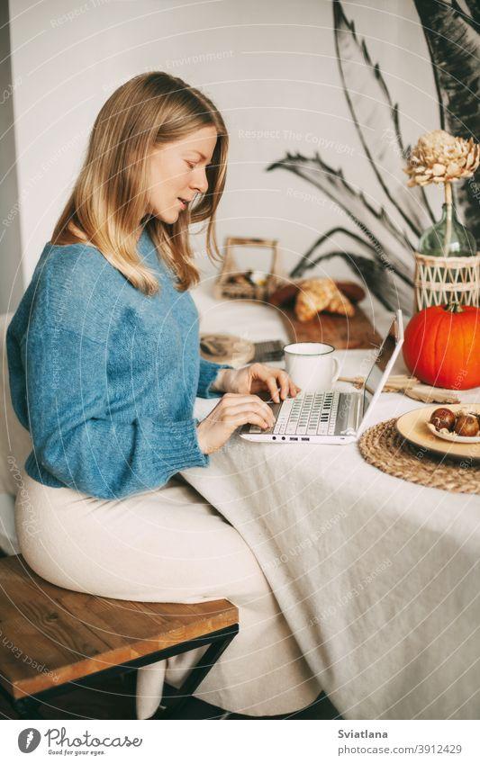 Nettes blondes Mädchen, das am Morgen an einem Laptop arbeitet und Kaffee trinkt. Arbeit online, freiberuflich, soziale Distanz benutzend schön Küche Frau