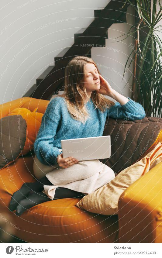 Pensive schönes Mädchen sitzt auf der Couch mit einem Laptop. Junge Frau arbeitet zu Hause mit Laptop. Arbeit online, freiberuflich, soziale Distanz Computer