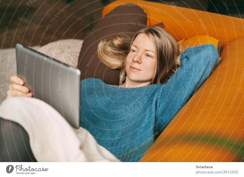 Glückliches Mädchen liegt auf einem bequemen Sofa im Wohnzimmer und schaut einen Film auf einem Tablet. Eine junge Frau ruht sich aus und kommuniziert mit Freunden über ein Tablet. Arbeit online, freiberuflich, soziale Distanz