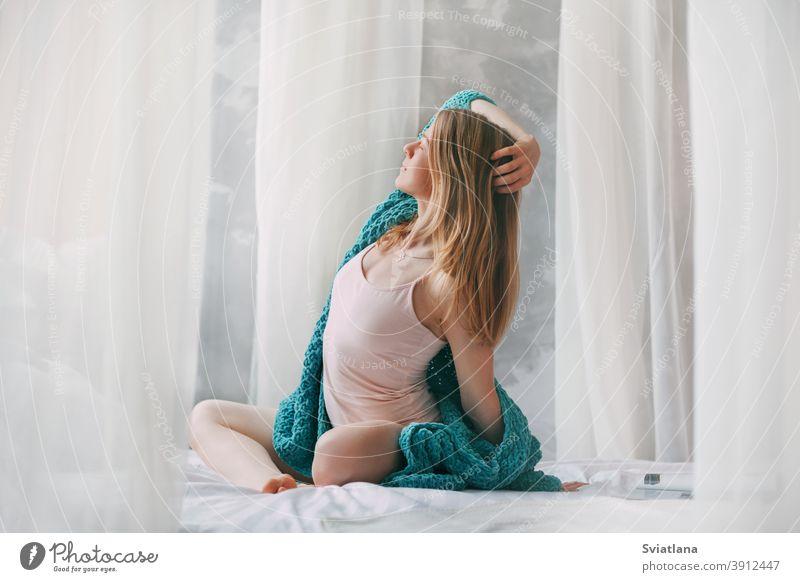 Nettes Mädchen sitzt im Schneidersitz auf dem Bett am Morgen. Junge Frau im Pyjama sitzt auf dem Bett nach dem Aufwachen schön jung Sitzen Morgen Wecken