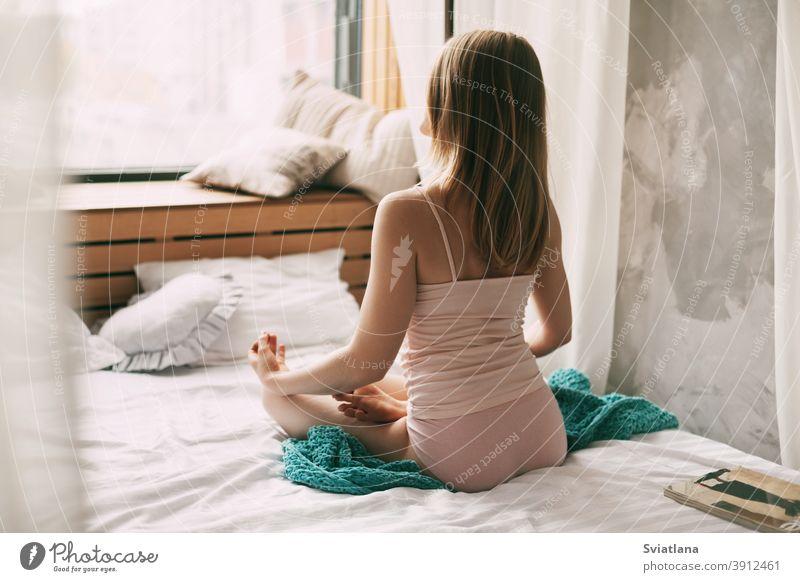 Eine junge Frau im Pyjama sitzt auf einem Bett in der Lotus-Position, die Finger in einer Mudra-Geste gefaltet, und genießt einen Morgen tiefer Achtsamkeitsmeditation. Rückansicht