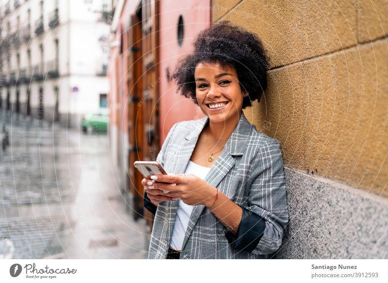 Hübsche Afro Frau mit Telefon in die Kamera schauen Afro-Look Porträt schwarze Frau per Telefon Straße Stadtleben Lächeln Funktelefon Smartphone benutzend