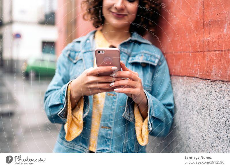 Junge Frau mit Telefon Kaukasier krause Haare unerkannt gesichtslos jung per Telefon Straße Stadtleben Lächeln Glück Funktelefon Smartphone benutzend Mitteilung