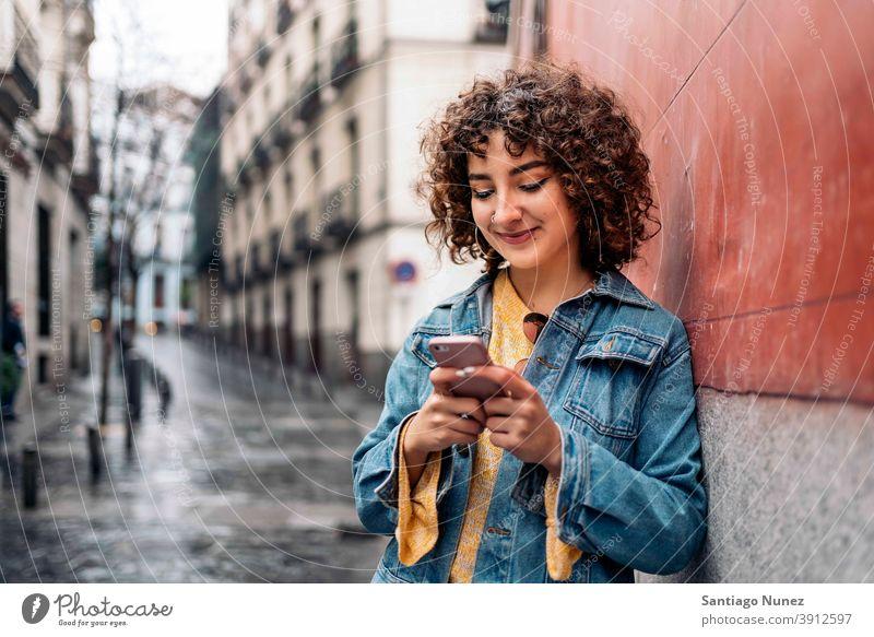 Junge Frau mit Telefon krause Haare jung Straße Kaukasier per Telefon Funktelefon Smartphone benutzend Mitteilung Technik & Technologie Typ Tippen Texten