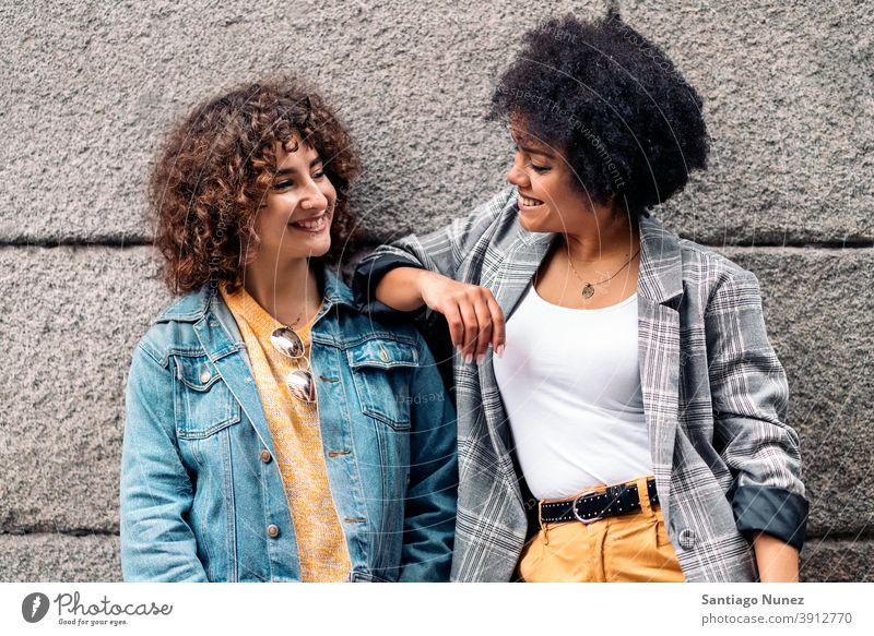 Cool Afro Mädchen und Freund lächelnd Frauen die sich gegenseitig ansehen Straße multiethnisch Afro-Mädchen Kaukasier Porträt Spaß haben Vorderansicht Freunde