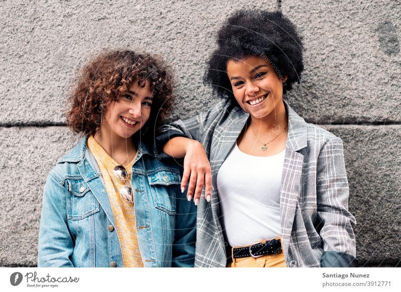 Cool Afro Mädchen und Freund lächelnd Frauen in die Kamera schauen Straße multiethnisch Afro-Mädchen Kaukasier Porträt Spaß haben Vorderansicht Freunde