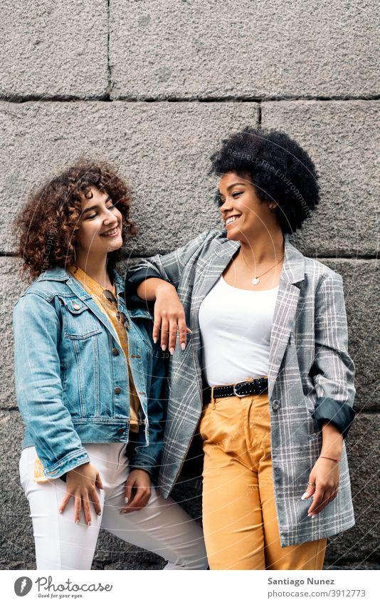 Cool Afro Mädchen und Freund in Straße Frauen die sich gegenseitig ansehen multiethnisch Afro-Mädchen Kaukasier Porträt Spaß haben Vorderansicht Freunde