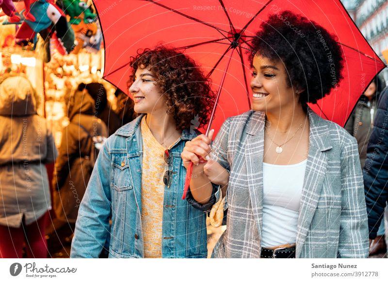 Fröhliche Freunde im Regentag Regenschirm Afro-Mädchen schwarze Frau Kaukasier Stadtleben Lächeln Vorderansicht Porträt Frauen Blick Straße multiethnisch
