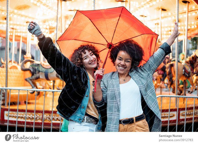 Fröhliche Freunde an einem regnerischen Tag Regenschirm Regentag Afro-Mädchen schwarze Frau Kaukasier Stadtleben Lächeln Vorderansicht Porträt Frauen