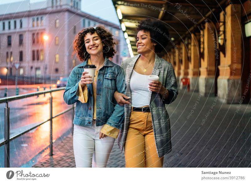 Afro Mädchen und Freund in Straße Tasse Kaffee laufen Freunde trinken Frauen multiethnisch Afro-Mädchen Kaukasier Porträt Spaß haben Vorderansicht Freundschaft