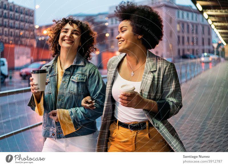 Afro Girl und Freund haben Spaß Tasse Kaffee laufen Straße Freunde trinken Frauen multiethnisch Afro-Mädchen Kaukasier Porträt Spaß haben Vorderansicht