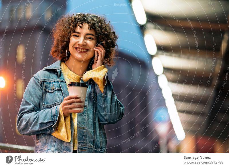 Glückliche junge Frau mit Telefon copyspace Stehen per Telefon Telefonanruf Aufruf Tasse Kaffee Vorderansicht Porträt Mädchen 20s krause Haare Straße Kaukasier