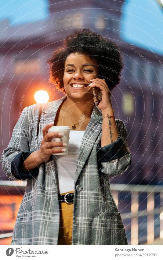 Glücklich Afro Frau mit Telefon Stehen per Telefon Telefonanruf Aufruf Tasse Kaffee Vorderansicht Afro-Look Porträt schwarze Frau Straße Stadtleben Funktelefon