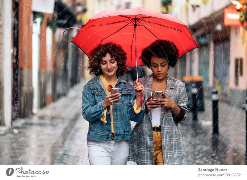 Glückliche Freunde mit Telefon Regenschirm Regentag Afro-Mädchen schwarze Frau Kaukasier per Telefon Stadtleben Lächeln Vorderansicht Porträt Frauen Blick