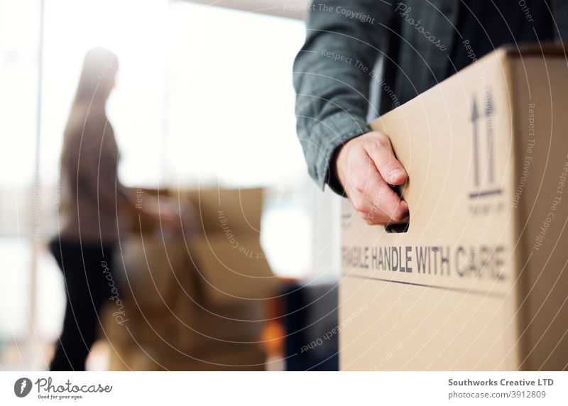 Close Up Of Man Carrying Removal Box As Couple Move In Or Out Of New Home Paar junges Paar Hauskauf Verpackung ausrückend Umzug Aufrüstung tragen Kasten
