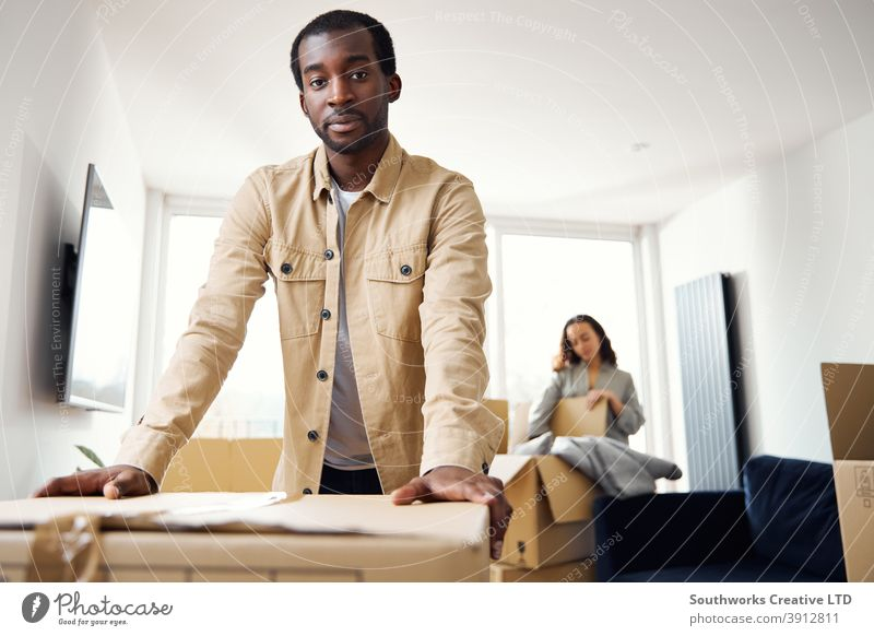 Porträt des jungen Paares im neuen Zuhause Auspacken Umzugskartons in Lounge zusammen junges Paar Hauskauf Kisten heimwärts neues Zuhause erste Wohnung Einzug