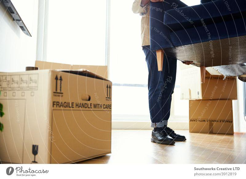 Close Up Of Man In New Home Carrying Sofa in Lounge On Moving Day Surrounded by Umzugskartons Mann junge Männer Hauskauf tragen Heben Möbel Wohnzimmer räkeln
