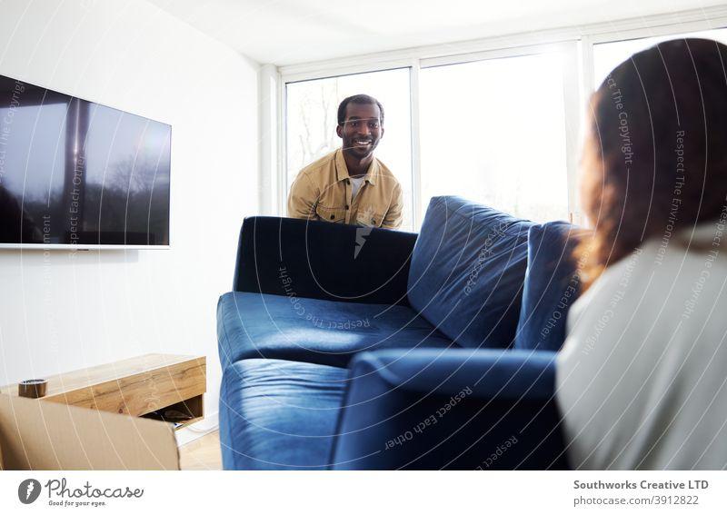 Junges Paar im neuen Zuhause trägt Sofa im Wohnzimmer am Umzugstag umgeben von Umzugskartons junges Paar Hauskauf tragen Heben Möbel räkeln Auspacken Kisten