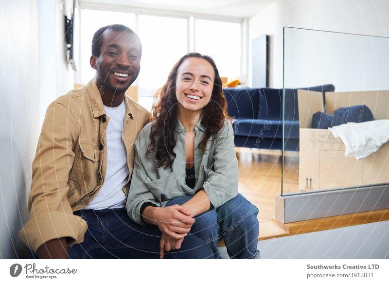Porträt des jungen Paares, das in ein neues Haus umzieht und auf dem Boden im Wohnzimmer mit Umzugskartons sitzt junges Paar Hauskauf in die Kamera schauen