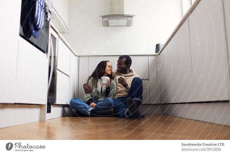 Junges Paar feiert den Umzug in ein neues Haus, das auf dem Boden mit einem heißen Getränk in der Küche sitzt junges Paar Hauskauf trinken Heißgetränk