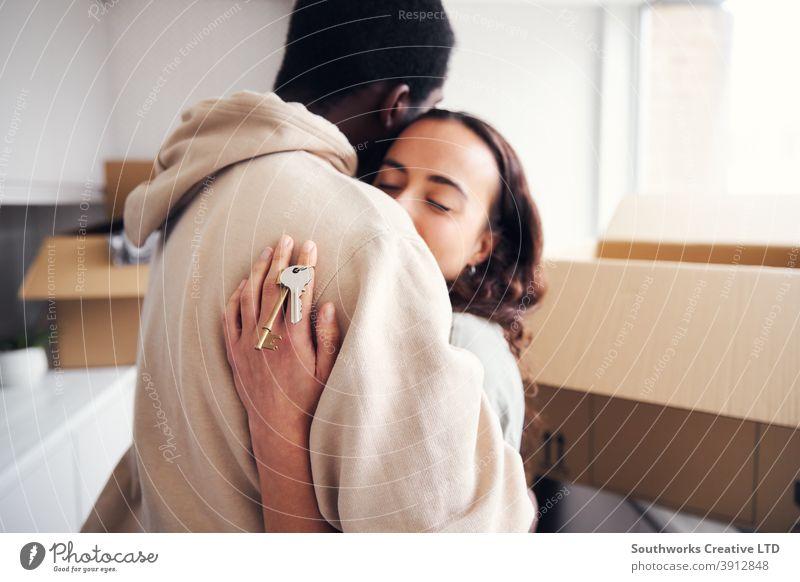 Junges Paar mit Schlüssel zu neuem Zuhause umarmt, als sie Umzugskartons in der Küche zusammen auspacken junges Paar Hauskauf Auspacken Kisten Beteiligung