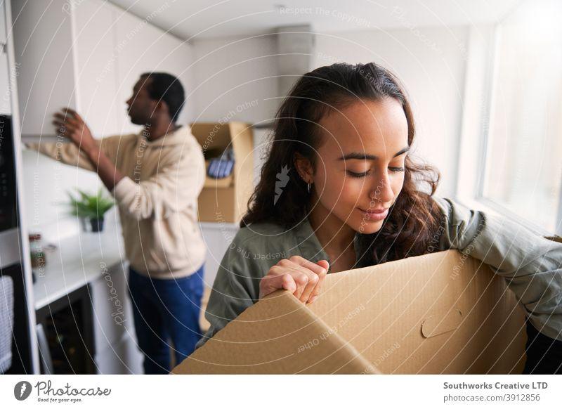 Aufgeregtes junges Paar in neuem Haus Auspacken Umzugskartons in der Küche zusammen Hauskauf Kisten heimwärts neues Zuhause erste Wohnung Einzug Umzugstag
