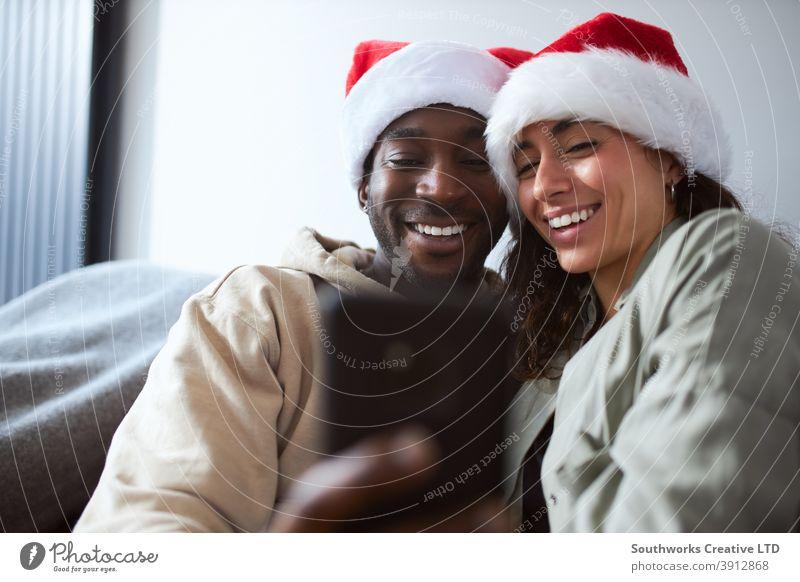 Junge lächelnde Paar trägt Santa Hüte zu Hause posieren für Weihnachten Selfie auf Handy zusammen junges Paar posierend Weihnachtsmann Hut tragend Sitzen Sofa