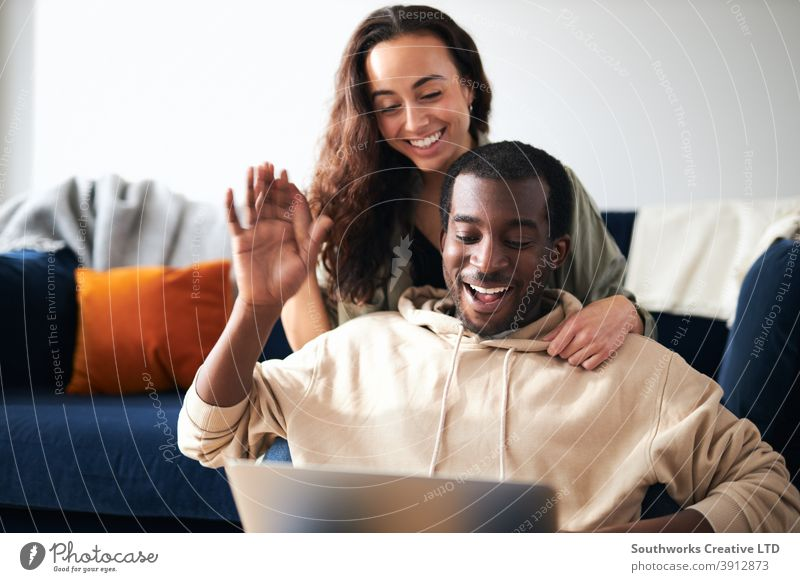 Entspanntes junges Paar zu Hause sitzen auf Sofa machen Videoanruf auf Laptop-Computer Video-Chat Mitteilung winkend Familie Freunde Eltern Sitzen räkeln