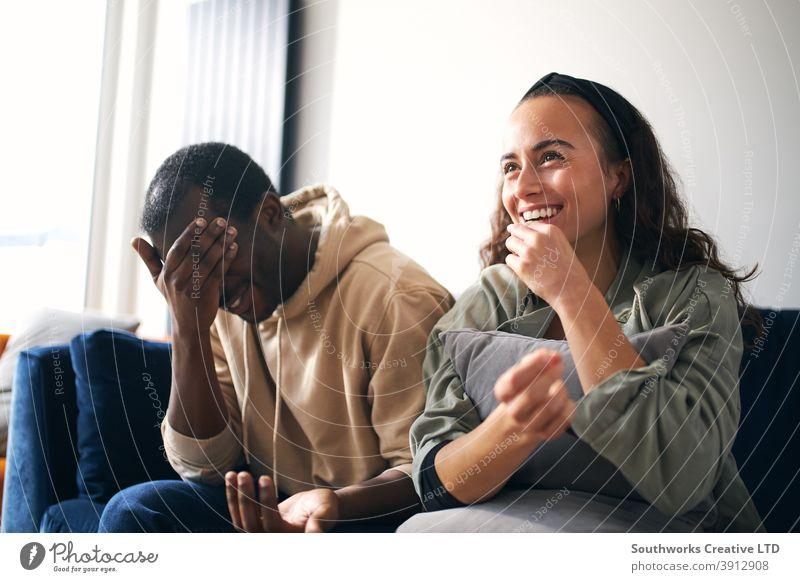 Lächelndes junges Paar, das sich zu Hause auf dem Sofa sitzend entspannt, während es gemeinsam einen Film im Fernsehen ansieht Sitzen räkeln zuschauend