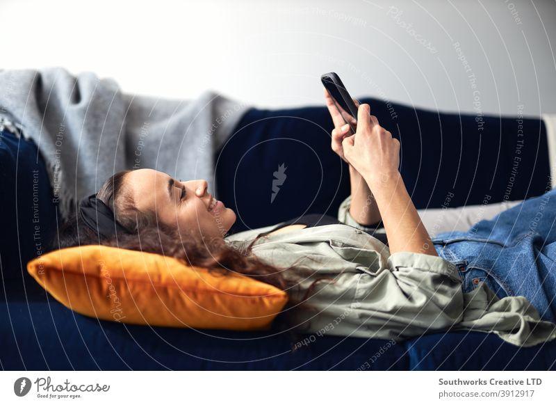 Junge lächelnde Frau entspannt sich zu Hause auf dem Sofa liegend und überprüft soziale Medien auf dem Handy Lügen räkeln Mobile Zelle Smartphone Technologie