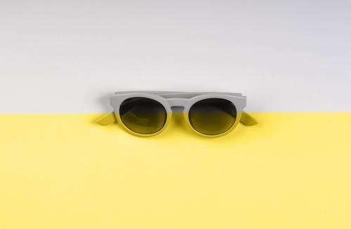 Leuchtende gelbe und graue Sonnenbrillen-Kulisse Duoton lichtvoll Farbe Mode Split Jahr endgültig Brille Hintergrund modern Sommer trendy Objekt sehr wenige