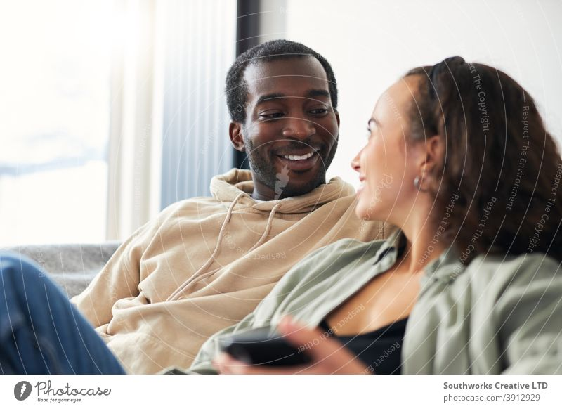 Junges lächelndes Paar entspannt sich zu Hause auf dem Sofa sitzend und überprüft soziale Medien auf Mobiltelefonen zusammen junges Paar Sitzen räkeln Mobile