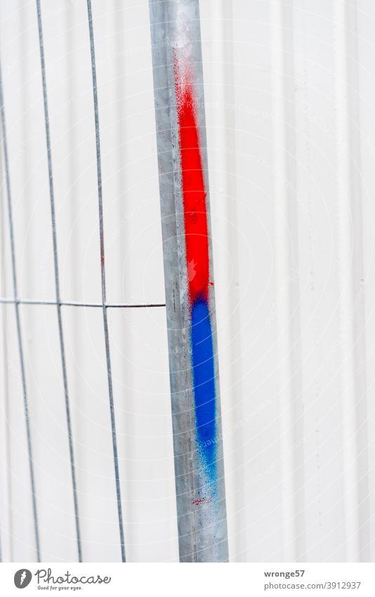 Rote und blaue Farbmarkierung an eine Bauzaun vor einem hellgrauen Container im Hintergrund rote und blaue Markierung rotblau Kennzeichnung Baustelle